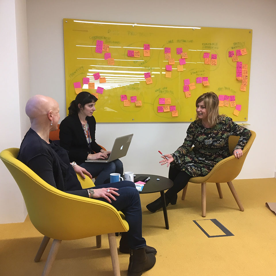Team discusses UX with post-it notes on a notice board