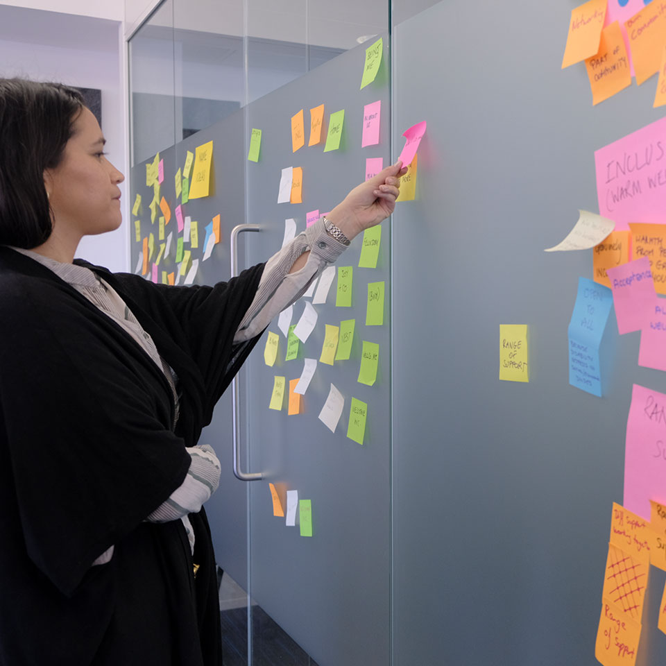 A woman puts a post-it note on a wall