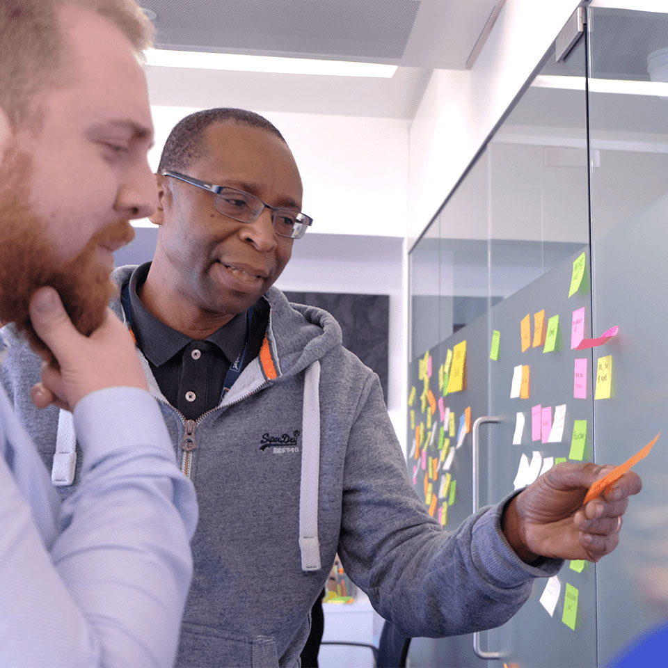 Two men put post-it note on a wall thinking about UX